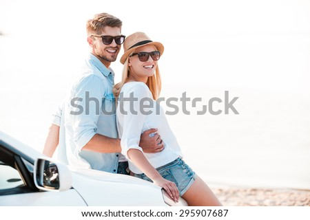 Enjoying quality time together. Side view of smiling young couple bonding and looking at camera while leaning at the hood of their white convertible - stock photo