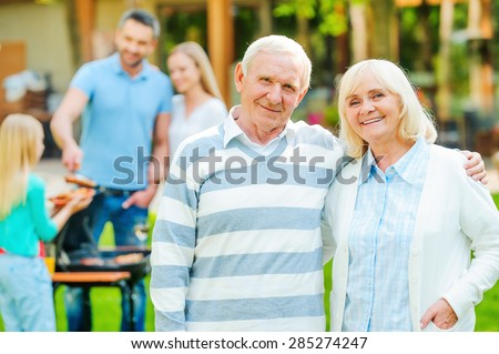 Enjoying quality time with family. Happy senior couple bonding to each other and looking at camera while other members of family barbecuing food in the background  - stock photo