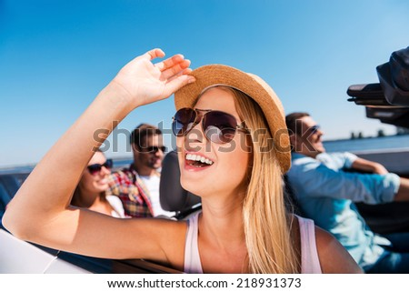 Enjoying road trip. Group of young happy people enjoying road trip in their convertible while beautiful woman adjusting her hat and smiling - stock photo
