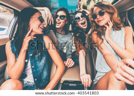 Enjoying road trip together. Four beautiful young cheerful women looking happy and playful while sitting in car  - stock photo