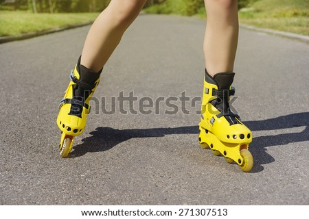 Enjoying roller skating rollerblading on in line skates sport in park. Outdoor activities. Part of human legs in sport shoes. - stock photo