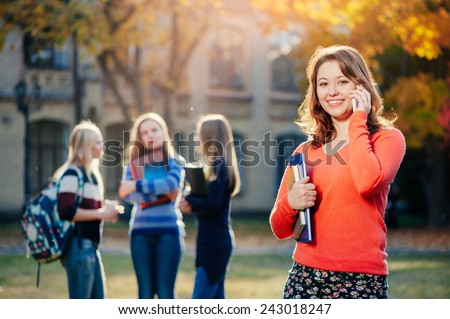 Enjoying student life. Beautiful young woman talking on the mobile phone and smiling while standing against university building with her friends chatting in the background - stock photo