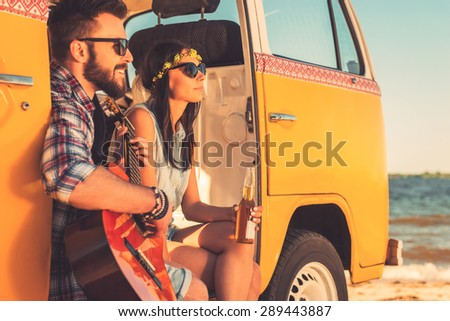 Enjoying summer day togehter. Cheerful young couple enjoying time together while sitting in their retro minivan with sea in the background  - stock photo