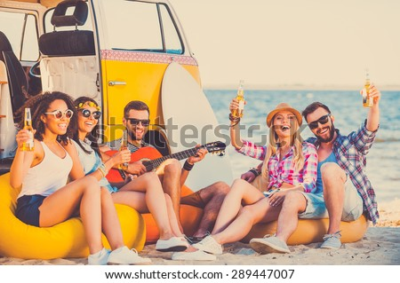 Enjoying summer time together. Group of happy young people having fun together while sitting on the beach near their retro van - stock photo