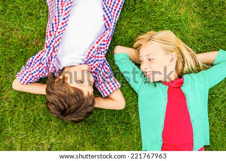 Enjoying summer time. Top view of two cute little children holding hands behind head and looking at each other with smile while lying on the green grass together - stock photo