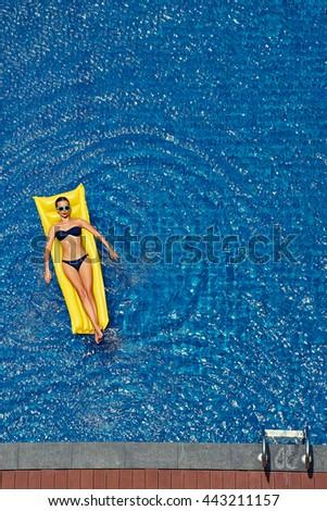 Enjoying suntan. Vacation concept. Top view of slim young woman in bikini on the yellow air mattress in the big swimming pool. - stock photo