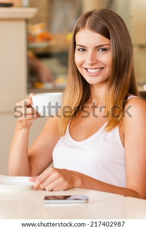 Enjoying the best coffee in town. Attractive young woman drinking coffee and smiling while sitting in coffee shop - stock photo