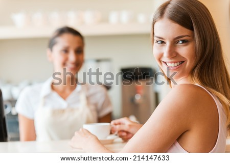 Enjoying the best coffee in town. Beautiful young smiling woman holding coffee cup and looking over shoulder while female barista standing in the background - stock photo