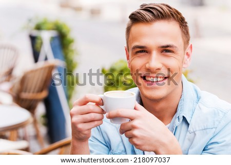 Enjoying the best coffee in town. Cheerful young man drinking coffee and smiling while sitting in sidewalk cafe - stock photo