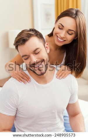 Enjoying the best massage. Beautiful young loving couple sitting together in bed while woman massaging her boyfriend - stock photo