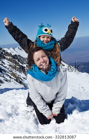Enjoying the first snow in the mountains - woman and little girl on a cliff - stock photo