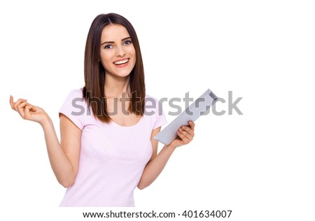Enjoying the modern technologies. Beautiful cheerful young woman using her tablet with smile while standing over white background - stock photo