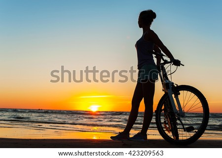 Enjoying the moment. Young sporty woman cyclist silhouette contemplating the sunset on blue sky background on the beach. Summertime multicolored outdoors horizontal image. - stock photo
