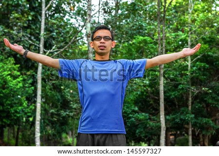 Enjoying the nature. Young man arms raised enjoying the fresh air in green forest. - stock photo