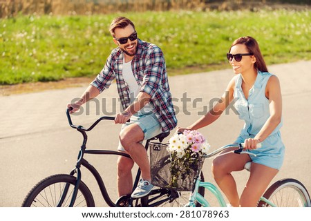 Enjoying the summer bike ride. Cheerful young couple riding on bicycles along the road - stock photo