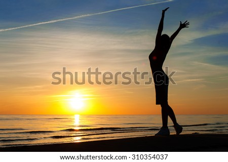 Enjoying the summer evening. Cheerful slender woman silhouette contemplating the sunset with raised up hands on blue sky background on the beach. Summertime multicolored outdoors horizontal image. - stock photo