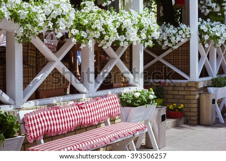Enjoying the warm bright summer in the style of Provence. Happy summer. Summer journey. Street in the style of Provence. Facade with wooden furniture, flower pots, benches with soft cushions - stock photo