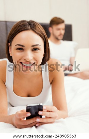 Enjoying their free time at home. Beautiful young woman holding mobile phone and smiling while lying in bed with man working on laptop in the background - stock photo