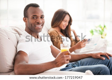 Enjoying their free time together. Handsome young African man sitting on the couch and holding a glass of orange juice while his wife sitting on the background  - stock photo