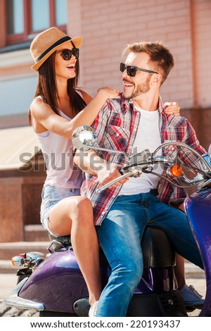 Enjoying their time together. Beautiful young couple sitting on scooter together while handsome man looking over shoulder and smiling - stock photo