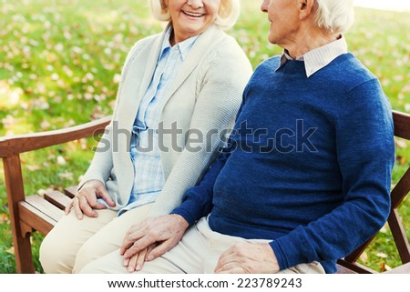 Enjoying their time together. Close-up of happy senior couple holding hands and looking at each other while sitting on the bench in park together  - stock photo