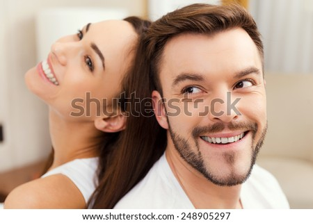 Enjoying time together. Cheerful young loving couple sitting back to back and smiling - stock photo