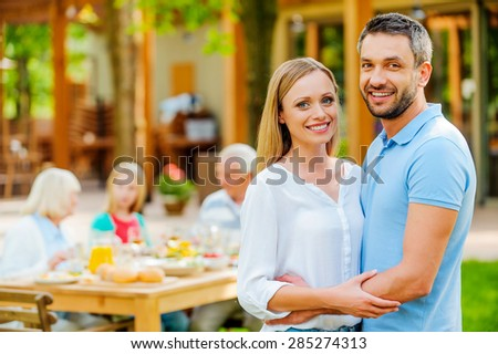 Enjoying time with their nearest. Happy young couple bonding to each other and smiling while their family sitting at the dining table in the background  - stock photo