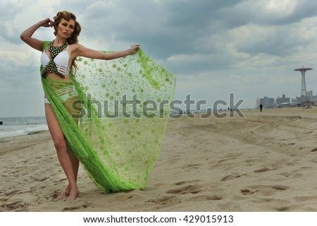 Enjoyment. Fashion model woman in design bikini with blowing cover up posing pretty on the beach. - stock photo