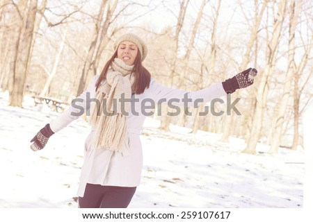 Enjoyment Happy Lovely Relaxing Young Woman Enjoying Winter. Portrait at beautiful sunny winter day in the park. Caucasian carefree female with spreading hands wintertime season outdoor. - stock photo