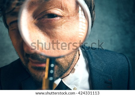 Enlarged eye of tax inspector looking through magnifying glass, inspecting offshore company financial papers, documents and reports. - stock photo