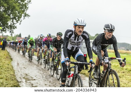 ENNEVELIN, FRANCE - JUL 09:The cyclists Dries Devenyns (Giant-Shimano) and Haimar Zubeldia (Trek ) riding on a cobbled road during the stage 5 of Le Tour de France in Ennevelin on July 09 2014. - stock photo