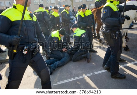 ENSCHEDE, THE NETHERLANDS - FEB 13, 2016: A demonstrator against a huge migrant refugee camp for refugees is being arrested by policemen. - stock photo