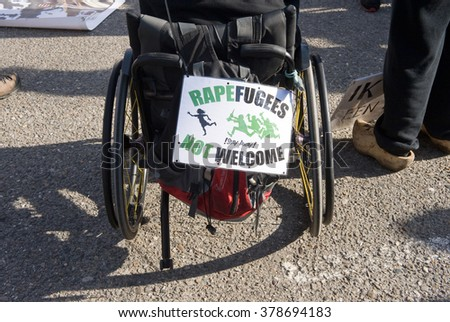 ENSCHEDE, THE NETHERLANDS - FEB 13, 2016: An invalid in a wheelchair is demonstrating against a huge migrant refugee camp for muslim war refugees close to the part of the city where people live. - stock photo