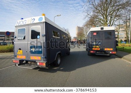 ENSCHEDE, THE NETHERLANDS - FEB 13, 2016: People are demonstrating against a huge migrant refugee camp for syrians close to the part of the city where they live. Police are watching them. - stock photo