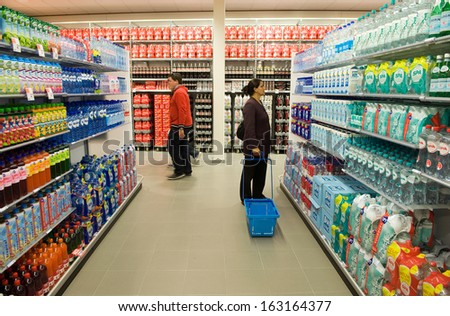 ENSCHEDE, THE NETHERLANDS - JUNE 27: People are looking, walking and shopping in the Albert Heijn supermarket between al the products in a gangway , June 27, 2013 in the Netherlands. - stock photo