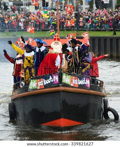 ENSCHEDE, THE NETHERLANDS - NOV 14, 2015: The dutch Santa Claus called 'Sinterklaas' is arriving with his help Black Pete on a steamboat in a harbor in Holland. - stock photo