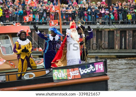 ENSCHEDE, THE NETHERLANDS - NOV 14, 2015: The dutch Santa Claus called 'Sinterklaas' is arriving with his helpers Black Pete on a steamboat in a harbor in Holland. - stock photo