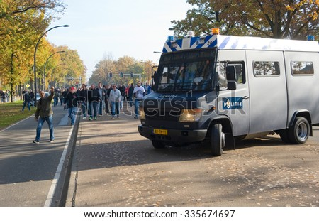 ENSCHEDE, THE NETHERLANDS - OCT 31, 2015: People are demonstrating against a huge migrant refugee camp for syrians close to the part of the city where they live. Police are watching them. - stock photo