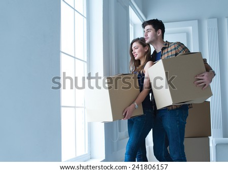 Entering new house. Young and beautiful couple is moving to new apartment surrounded with plenty of cardboard boxes. Both are looking in the window and holding boxes - stock photo