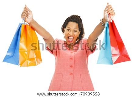 Enthusiastic african-american woman holding up her shopping bags.  Isolated on white. - stock photo