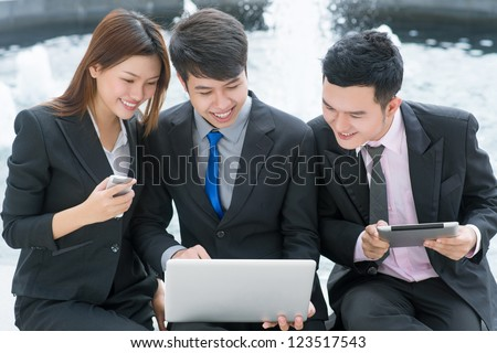 Enthusiastic business people communicating via different gadgets - stock photo