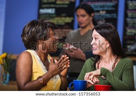 Enthusiastic Hispanic woman talking with friend in cafe - stock photo