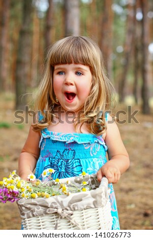 Enthusiastic little girl holding a basket of flowers in  forest - stock photo