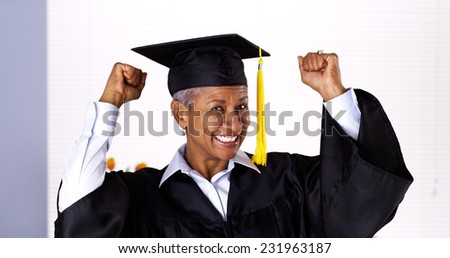 Enthusiastic mature black woman in graduation gown - stock photo