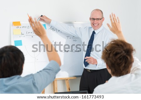 Enthusiastic students raising their hands to answer the question - stock photo