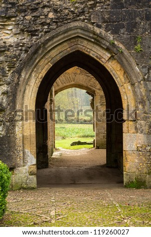 Entrance arches of Minster Lovell in Cotswold village with graveyard - stock photo