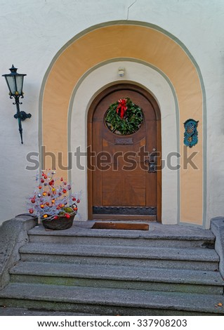 Entrance decorated for the holidays with wreath and red bow. Garmisch-Partenkirchen, small Bavarian town in south Germany. - stock photo