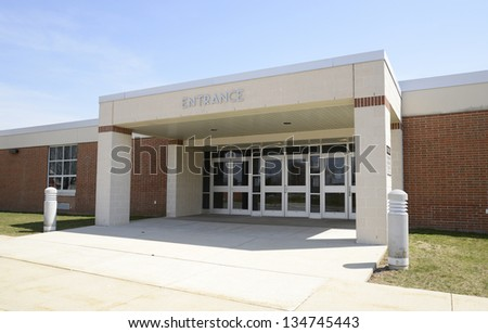 entrance for a modern school, with a covered entryway and sidewalk - stock photo