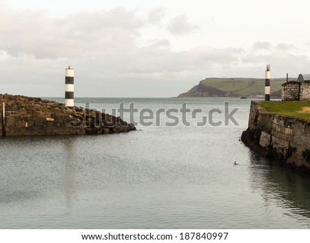Entrance from the shelter behind the solid sea wall at Carnlough Harbor in Northern Ireland - stock photo
