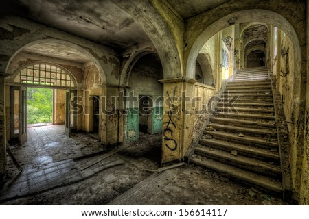 entrance hall of a decayed building - stock photo